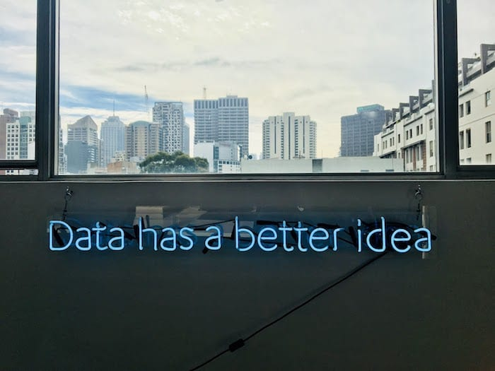 """neon sign that reads """"data has a better idea."""" skyline in the background"""