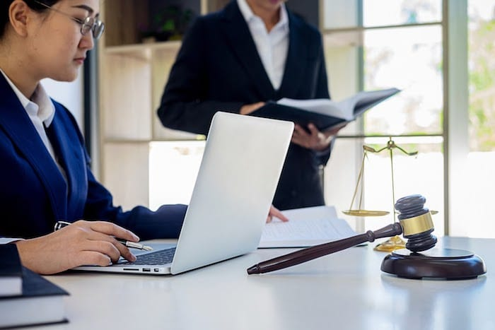 A business woman typing on her laptop, sitting at a table with a gavel, man reading book in the background